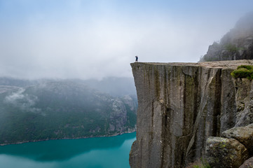 Tourist standing at Prekestolen rock's edge.