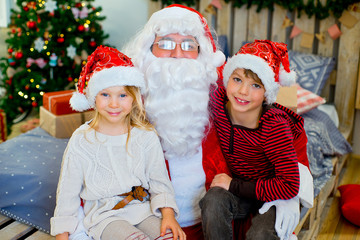 Santa Claus and two children sitting on the bed