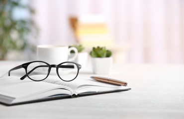 Glasses and open notebook on wooden table. Healthy eyes concept