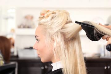 Hairdresser drying blonde's hair at salon
