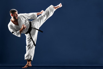 Karate man in a kimono hits foot on a blue background
