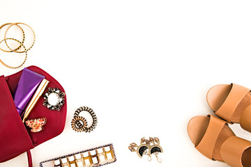 Flat lay of glamour beauty accessories on a white background. Marsala bag, makeup, jewelry, perfumes, spiral hair ties and nude high heels shoes.