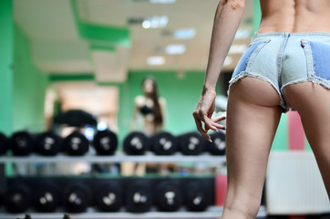 Athletic girl in a sports suit is engaged in activities in the gym. Fitness classes under the guidance of coach, a healthy lifestyle. The concept of activity gyms. Sports training in equipped room