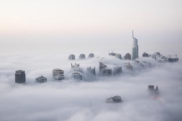 Rare early morning winter fog above the Dubai Marina skyline and skyscrapers ahead of sunrise in Dubai, United Arab Emirates.