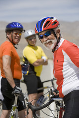 Portrait of a happy senior male cyclist with friends standing in the background