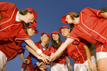 Happy female softball players stacking hands against clear blue sky