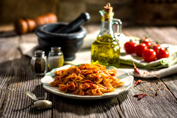 Pasta with tomato sauce on wooden background