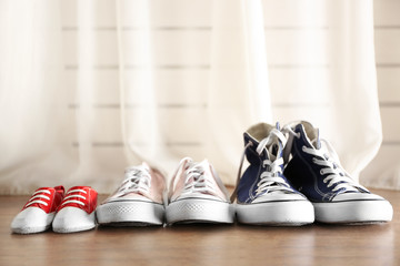 Family concept. Shoes for parents and child on floor in the room