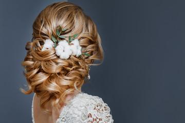 piękna fryzura ślubna ozdobiona kwiatem bawełny, widok z tyłu