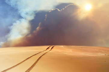 Vehicle tracks through desert and dunes leading into a sand, smoke and cloud filled sky.