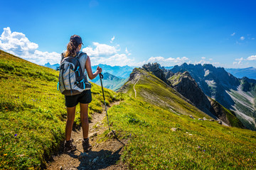 Hiker in boots and backpack holds walking stick