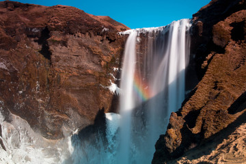 Iceland Skogafoss waterfall in winter with a rainbow and snow and ice frozen spray and birds
