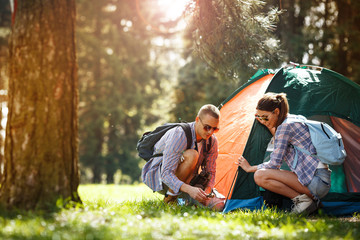 Young campers setting up the tent at the forest.