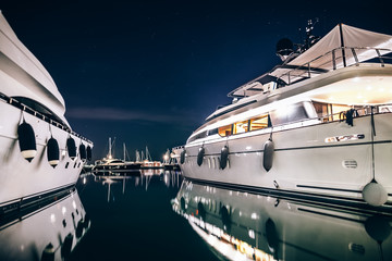Luxury yachts in La Spezia harbor at night with reflection in wa