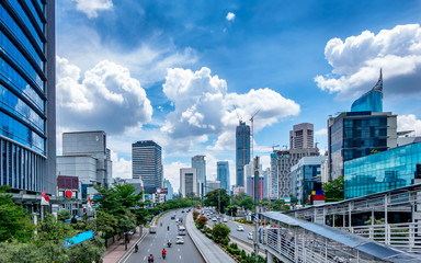 Beautiful skyline of Jakarta, Indonesia. Showing modern skyscraper buildings and beautiful blue sky and white cloud at daylight and big road with moderate traffic. Captured in Jend. Sudirman Street.