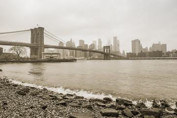Brooklyn Bridge at foggy day, New York, winter 2016. Sepia toning.