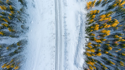 Top view at the wintry two way rail road in evergreen forest