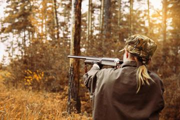 Jesienny sezon polowań. Kobieta myśliwy z pistoletem.