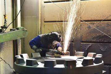 Industriearbeiter schleift Werkstück aus Metall mit einer Flex - Gussteil in einer Giesserei // Industrial worker grinds work piece of metal with a flex casting in a foundry