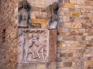 Medieval religious art outside church, Fornovo di Taro, near Parma, Italy. Men fighting.