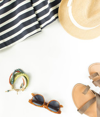 Summer fashion, summer outfit on white background. Blue striped dress, brown sandals, retro sunglasses, straw hat, wod bracelet. Flat lay, top view