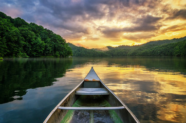 Summer sunset, mountain lake, aluminum canoe