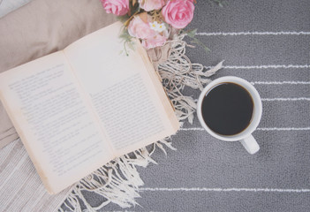 relax coffee cup of hot drink and read a book on gray carpet.