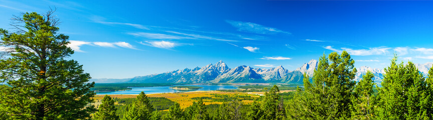 Grand Teton National Park, Wyoming.  Grand Tetons mountain range blue sky.  Panorama