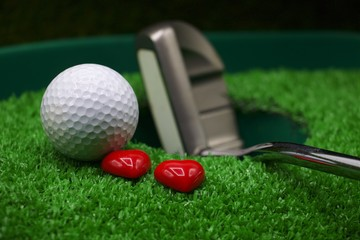 Golf ball and putter with heart are on green grass