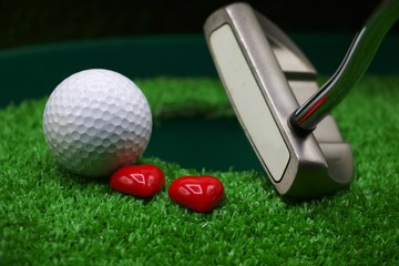 Putting golf ball and hearts with putter