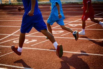 Group of boys running on running track in the stadium