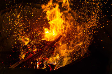 fiercely burning pieces of wood with blurred swirling sparks on black background