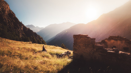 Girl is sitting on a stone and watching sunrise in mountains