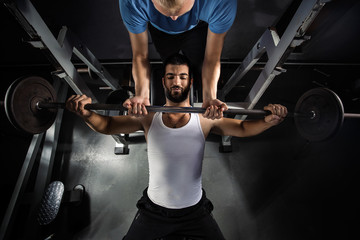 Muscular young man is exercising in the gym with his personal fitness instructor. He is doing bench workout.