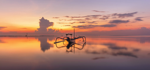 Wschód słońca przy Sanur Beach Bali, Indonezja z tradycyjną balijską łódką jukung