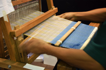 Thai people using small loom or weaving machine for weaving show