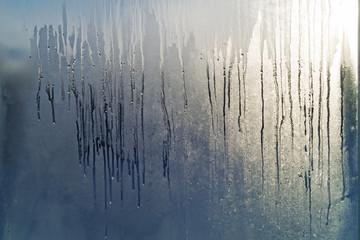 Frozen window glass melts in the sun. Spring.