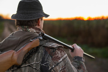 Hunter with rifle over his shoulder