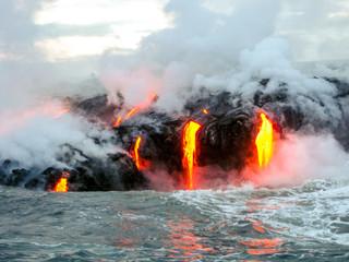 Denny widok Kilauea wulkan w Dużej wyspie, Hawaje, Stany Zjednoczone. Niespokojny wulkan, który istnieje na rynku od 1983 roku. Zdjęcie zrobione o zachodzie słońca, gdy lawa świeci w ciemności, gdy skacze do morza.