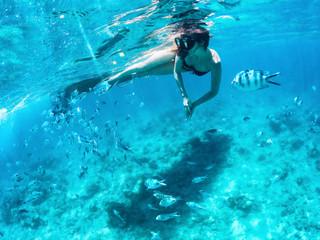 Piękna kobieta snorkeling wśród ryb w błękitnym oceanie.