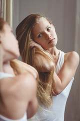 Teenage girl checking her face and hairs in the mirror