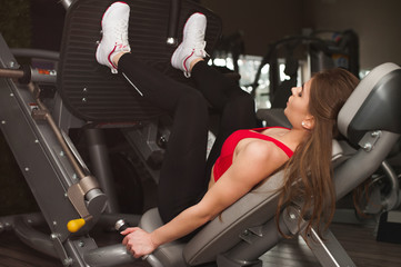 Strong young woman doing fitness exercises for legs muscles in gym, leg press