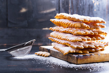 Frappe   - typical Italian carnival fritters dusted with powdered sugar on   old black wooden table. With free text space.