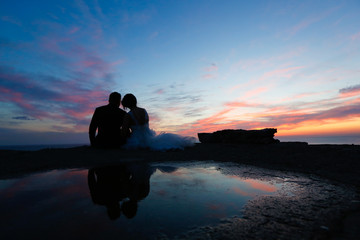 Groom and bride kissing at dusk
