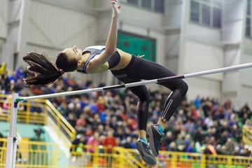 Młoda profesjonalna sportsmenka skacze nad barem w konkursie wzwyż przeciwko zatłoczonej trybunie.