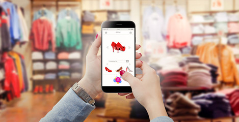 Women in clothing store holding phone in hands and searching online shoes