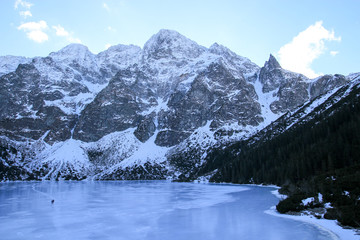 Panorama of frozen lake surrounded by mountains. People walk on the ice