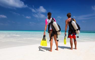 Taucher Paar am Strand schaut auf den Ozean