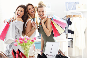 Group of happy friends shopping in store