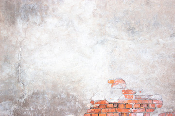 brick wall with damaged plaster, background shattered cement surface